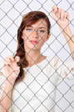 La femme dans la robe reste derrière la maille en métal et la retient Photos libres de droits