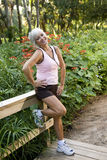 La femme dans la séance d'entraînement vêtx la position sur la passerelle de stationnement Images stock