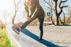 La femme dans la veste et des espadrilles fait des exercices de sports en parc dedans Photos libres de droits