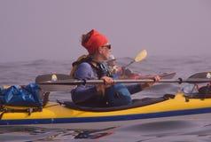 La femme dans le bandana rouge barbote le kayak de mer en brouillard photographie stock