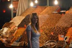 La femme dans le bazar la nuit, devant un support des desserts de fruits secs et de miel Image stock