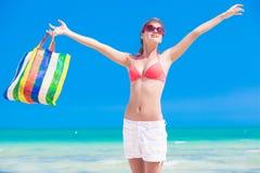 La femme dans le bikini et les lunettes de soleil avec la plage mettent en sac Photo libre de droits