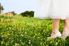 La femme dans le blanc a lacé la robe nuptiale et les chaussures blanches au gisement jaune de fleur placé sur les falaises de la Image stock