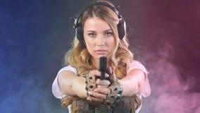 La femme dans le blindage tient le revolver en mains Arm?e, d?vouement, technologie Mouvement lent banque de vidéos