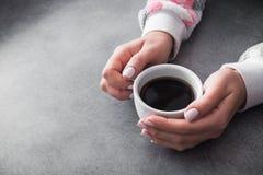la femme dans le chandail chaud tient une tasse de café blanche Photos libres de droits