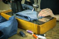 La femme dans le chandail noir travaille à la vieille machine à coudre Images stock