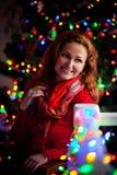 La femme dans le chandail rouge s'assied sur un fond de l'arbre de Noël avec les lumières et la balustrade décorée et le sourire Image stock