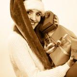 La femme dans le chapeau d'aide de Santa tient des boîte-cadeau Image libre de droits