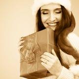 La femme dans le chapeau d'aide de Santa tient le boîte-cadeau Images libres de droits