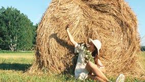 La femme dans le chapeau de paille avec des fleurs prend un selfie dans un pré clips vidéos