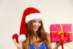 La femme dans le chapeau du père noël tient le boîte-cadeau Temps de Noël Images stock