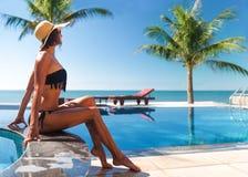 La femme dans le chapeau les prennent un bain de soleil près de la gâchette et de la piscine Photo libre de droits