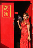 La femme dans le Chinois habillent la position à la porte rouge images stock