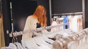 La femme dans le choix du vêtement dans le magasin d'habillement du ` s de femmes photos libres de droits
