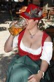 La femme dans le costume bavarois typique boit de la bière Image libre de droits