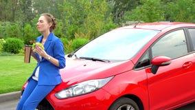 La femme dans le costume bleu s'assied sur le capot de la voiture rouge et prend le déjeuner La fille mange le sandwich et boit d banque de vidéos