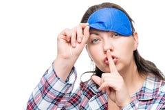 La femme dans le geste d'expositions de pyjamas se comportent silencieusement sur le blanc Photos stock