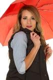 La femme dans le gilet noir et la prise rouge de parapluie investissent au-dessus du menton Images stock
