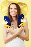 La femme dans le grand chapeau jaune d'été tient des bascules électroniques Images stock