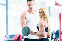La femme dans le gymnase avec le barbell a aidé par l'entraîneur de forme physique Image stock