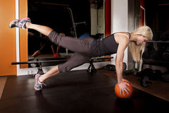 La femme dans le gymnase soulèvent la jambe vers le haut de la boule Photos stock