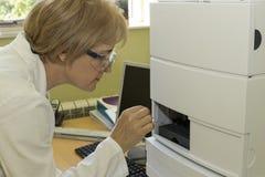 La femme dans le laboratoire ajoutent des échantillons à la CLHP Photos stock