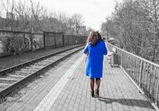 La femme dans le manteau bleu va pr?s du chemin de fer photographie stock libre de droits