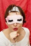 La femme dans le masque imite le chant dans un microphone Image libre de droits