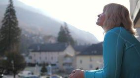 La femme dans le matin sur la véranda respire l'air frais de montagne et exhale la vapeur illustration stock