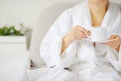 La femme dans le peignoir blanc à la table buvant une boisson chaude Photo stock
