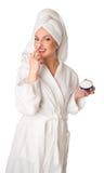 La femme dans le peignoir met la crème Photo libre de droits