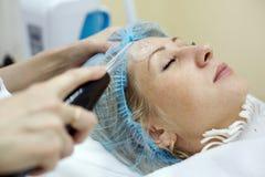 La femme dans le salon de beauté obtient la demande de règlement de peau de visage Photos stock