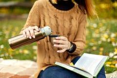La femme dans le sweather tricoté par brun verse le café chaud du thermos dans la tasse Lecture du livre intéressant en tout à fa images stock