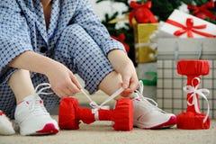 La femme dans les pyjamas et des chaussures sportives délie l'arc sur le dumbbe image stock