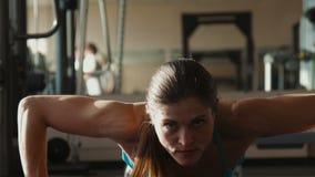 La femme dans les vêtements de sport fait des pousées dans un gymnase banque de vidéos