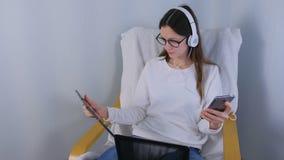 La femme dans les verres et des ?couteurs travaille sur l'ordinateur portable se reposant dans le fauteuil T?l?phone portable et  banque de vidéos