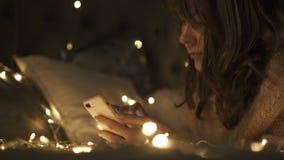 La femme dans la pièce décorée par Noël se trouve sur le lit avec le téléphone banque de vidéos