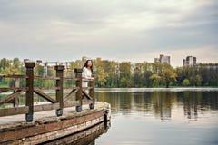 La femme dans la robe blanche se tient sur un pont de ponton en bois sur un lac de rivière avec un paysage urbain sur un fond images libres de droits