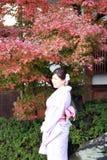 La femme dans la robe de kimono et la ceinture rose se tenant avec le rouge de fond part dans le jardin d'automne au temple de Ki photographie stock