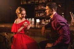 La femme dans la robe flirte avec l'homme dans la boîte de nuit Image stock