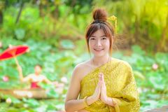 La femme dans la robe thaïlandaise d'or est bonjour dans le jardin de lotus images stock