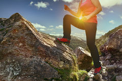 La femme dans s'élever rouge rejette le fonctionnement sur les montagnes au coucher du soleil Photos stock