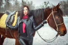 La femme dans un costume noir se tient près d'un cheval image stock