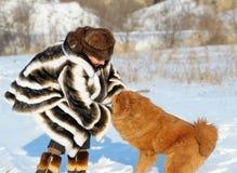 La femme dans un manteau de fourrure de vison joue avec un crabot Image stock