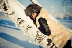 La femme dans un manteau de fourrure s'étendent sur l'arbre Image libre de droits