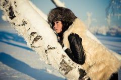 La femme dans un manteau de fourrure s'étendent sur le bouleau Photographie stock libre de droits