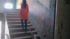 La femme dans un manteau rouge inspecte le bâtiment détruit après le tremblement de terre de catastrophe, inondation, le feu Mont banque de vidéos