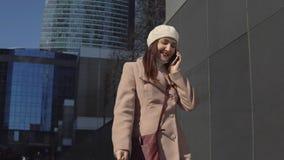 La femme dans un manteau va au centre de la ville, parlant au téléphone photo libre de droits