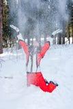 La femme dans un procès sportif jette en l'air vers le haut de l'in-field de neige Image stock