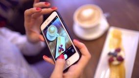 La femme dans un restaurant font la photo de la nourriture avec l'appareil-photo de téléphone portable Fermez-vous des mains avec banque de vidéos